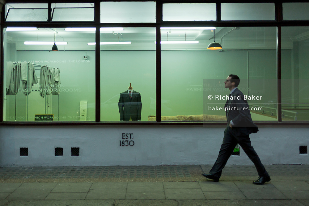 A man walks past the window of London Fashion Workrooms, a  on 4th December 2017, in London England. Established in 1892 as a formalwear manufacturer, The London Fashion Workrooms branched into alterations in the 1970s. The first large fashion workroom was launched in 1997 specifically to service the shops and boutiques of London's west end. Based in Covent Garden with a 4000 square foot purpose built unit, we presently provide garment alteration services to 38 high-end London stores and many private clients. With 20 tailors on site we have the skills and personnel necessary to provide a one-stop service for all your needs.