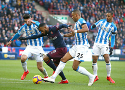 Arsenal's Alexandre Lacazette is tackled by Huddersfield Town's Christopher Schindler, left, and Huddersfield Town's Mathias Zanka Jorgensen, centre right