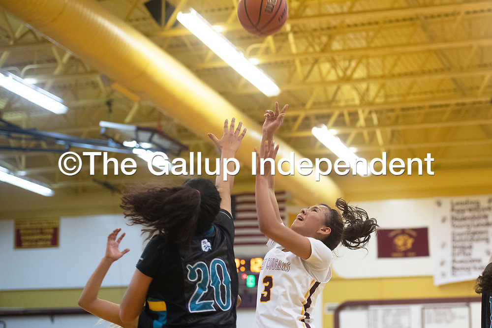 Tohatchi Cougar Krystal Benally (3) drives to the basket while Navajo Prep Eagle Aiona Johnson (20) defends at Tohatchi High School Thursday night in Tohatchi.