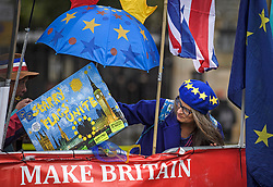 © Licensed to London News Pictures. 21/10/2019. London, UK. An anti-Brexit protestor holds up a painting and shelters underneath an umbrella outside the Houses of Parliament in Westminster, London. Last week Parliament sat on a Saturday for the first time since 1982, but failed to vote on Boris Johnson's new Brexit deal. Photo credit: Ben Cawthra/LNP