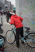 "A cyclist stops to read a map of Berlin near the former Checkpoint Charlie, the former border between Communist East and West Berlin during the Cold War. Many cycling rental companies operate in the city where pavements and streets include cycle lanes. The Berlin Wall was a barrier constructed by the German Democratic Republic (GDR, East Germany) starting on 13 August 1961, that completely cut off (by land) West Berlin from surrounding East Germany and from East Berlin. The Eastern Bloc claimed that the wall was erected to protect its population from fascist elements conspiring to prevent the ""will of the people"" in building a socialist state in East Germany. In practice, the Wall served to prevent the massive emigration and defection that marked Germany and the communist Eastern Bloc during the post-World War II period."