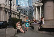 Lunchtime City workers, including a woman smoking, enjoy sunshine near the Bank of England during an unusual autumn heatwave on 13th September 2016, in the City of London, England.