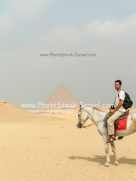 Tourists horse back riding in the Giza Plateau near the Great Pyramids of Egypt, Giza, Egypt. Model release available