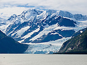 The tidewater Serpentine Glacier pours from the steep and glaciated Chugach Mountains into Harriman Fjord in Prince William Sound, Alaska, USA. Prince William Sound is surrounded by Chugach National Forest (the second largest national forest in the USA). Tour spectacular Prince William Sound by commercial boat from Whittier, which sits strategically on Kenai Peninsula at the head of Passage Canal. Whittier is a port for the Alaska Marine Highway System, a ferry service which operates along the south-central coast, eastern Aleutian Islands, and the Inside Passage of Alaska and British Columbia, Canada. Cruise ships stop at the port of Whittier for passenger connections to Anchorage (by road 60 miles) and to the interior of Alaska via highway and rail (the Denali Express). Known by locals as the Whittier tunnel or the Portage tunnel, the Anton Anderson Memorial Tunnel links Whittier via Portage Glacier Highway to the Seward Highway and Anchorage. At 13,300 feet long (4050 m), it is the longest combined rail and highway tunnel in North America. Whittier was severely damaged by tsunamis triggered by the 1964 Good Friday Earthquake, when thirteen people died from waves reaching 43 feet high (13 meters).