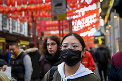 © Licensed to London News Pictures. 24/01/2020. LONDON, UK. A woman wears a facemask, possibly in reaction to the outbreak of the coronavirus in Wuhan, China as red lanterns decorate Chinatown ahead of Chinese New Year, the Year of the Rat.   Photo credit: Stephen Chung/LNP