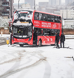 © Licensed to London News Pictures. 24/01/2021. London, UK. Police officers attend to a London bus stuck on a slope in Swiss Cottage, North London following heavy snowfall. Parts of the UK continue to suffer from flooding caused by Storm Christoph. Photo credit: Ben Cawthra/LNP