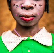 Best In Show<br /> <br /> Umou, 16, puts on her best clothes and lipstick for a baby naming ceremony in a small village in the Kalalé District of Benin. She is one of the few girls who goes to school past a young age. <br /> <br /> The economy is mainly based on agriculture with more than 95% of the population involved with farming. Despite its great potential, crop production in Kalalé remains weak and easily influenced by natural conditions. There is precious little rainfall during the six-month dry season that runs from November to April each year. During the dry season, the land of Kalalé is parched and its people are hungry. Malnutrition is widespread and most girls won't get access to education because the most pressing challenge for all the people of Kalalé is having enough food to eat. (photo by Ami Vitale)