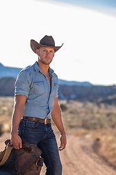 rugged good looking cowboy with a saddle on a rustic ranch with mountain views