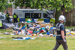 Licensed to London News Pictures. 17/06/2021. London, UK. Piles of tents, clothing and possessions are left in a heap as police and bailiffs clear an anti-lockdown camp on Shepherd's Bush Green this morning. The demonstrators who have been camping on the green since 31 May 2021 were forced out of their tents this morning with many of their possessions left behind as police in riot gear and on horseback forced everyone out of the west London green space. The protesters have been demonstrating against lockdown, mask wearing, vaccines and testing. Photo credit: Alex Lentati/LNP