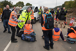 Enfield, UK. 15th September, 2021. A Metropolitan Police officer asks an Insulate Britain climate activist to move out of a slip road from the M25 at Junction 25 being blocked as part of a campaign intended to push the UK government to make significant legislative change to start lowering emissions. The activists, who wrote to Prime Minister Boris Johnson on 13th August, are demanding that the government immediately promises both to fully fund and ensure the insulation of all social housing in Britain by 2025 and to produce within four months a legally binding national plan to fully fund and ensure the full low-energy and low-carbon whole-house retrofit, with no externalised costs, of all homes in Britain by 2030 as part of a just transition to full decarbonisation of all parts of society and the economy.