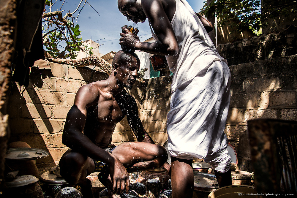 November 4, 2017. Before a tournamant Kherou Ngor's cousin blows water over the wrestler´s head at the Cham, the shrine of the ancestors of Kherou Ngor's family. They perform this ceremony in order to give Kherou Ngor the strenght and support of their anchestors for a fight