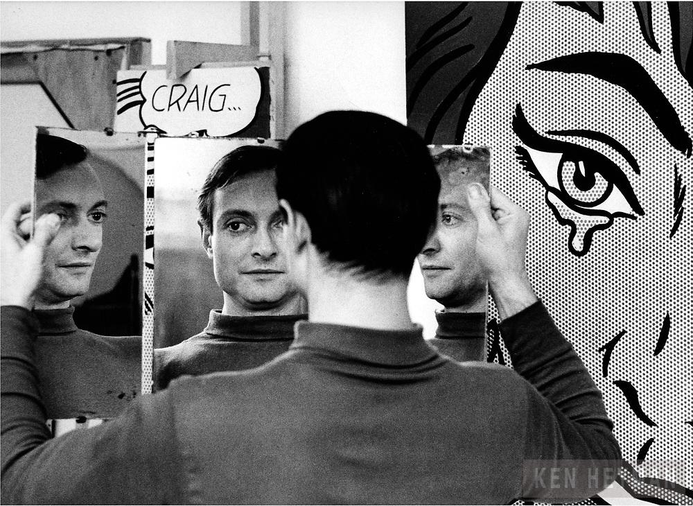 Roy Lichtenstein holding a mirror to get a better view of his work.