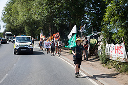 Harefield, UK. 26 June, 2020. Activists from HS2 Rebellion and Extinction Rebellion UK pass the Harvil Road protection camp on the 'Rebel Trail' hike along the route of the HS2 high-speed rail link from Birmingham to London. The activists, who departed from Birmingham on 20th June and will arrive outside Parliament in London on 27th June, are protesting against the environmental impact of the high-speed rail link and questioning the viability of the £100bn+ project.