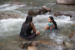 Cynthia Montes (r) bathes in the Guapinol river. Members of her community have been criminalised and imprisoned for protesting against a massive mining operation that affects the river.