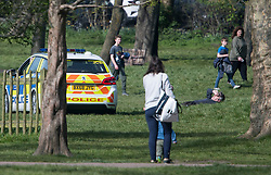 © Licensed to London News Pictures. 07/04/2020. London, UK. Police in a patrol car moving a man who is sunbathing in Queens Park, north west London, during a pandemic outbreak of the Coronavirus COVID-19 disease. The public have been told they can only leave their homes when absolutely essential, in an attempt to fight the spread of coronavirus COVID-19 disease. Photo credit: LNP