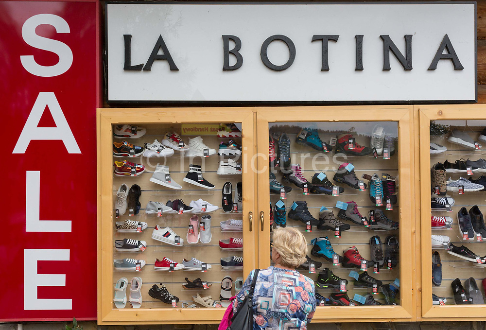 A local lady shopper looks at a display of a Polish shoe shop window, on 16th September 2019, in Zakopane, Malopolska, Poland.