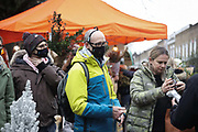 Shoppers wearing face masks queueing to pay at Columbia Road Flower Market on 6th of December 2020 in Hackney, London, United Kingdom. The flower market in East London is on all year around for all kinds of plants and flowers but at Christmas time, many come to buy their Christmas trees and decorations for the festive season. The national lockdown 2 has just ended and London is under tier 2. The pandemic is still raging so many wear face masks, even outside, because of the lack of social distancing.