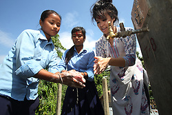 Sarah Nam Communications and Social Networking Officer,  Department of Water Supply and Sewerage (DWSS) with Lila Magar on the left and a friend, Sita SK  as they wash their hands at a water source at a NEWAH WASH water project in Puware Shikhar, Udayapur District, Nepal.