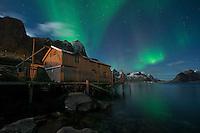 Northern Lights - Aurora Borealis shine in sky over abandoned Rorbu cabin, Valen, near Reine, Moskenesøy, Lofoten Islands, Norway