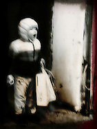 Blurred image of a little boy standing in a doorway holding a bag and yawning, Hanoi, Vietnam, Southeast Asia