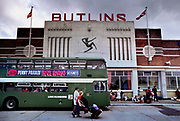 Thousands of arrivals for the Saturday turnaround in Butlins holiday camp, Skegness. Butlins Skegness is a holiday camp located in Ingoldmells near Skegness in Lincolnshire. Sir William Butlin conceived of its creation based on his experiences at a Canadian summer camp in his youth and by observation of the actions of other holiday accommodation providers, both in seaside resort lodging houses and in earlier smaller holiday campsThe camp began opened in 1936, when it quickly proved to be a success with a need for expansion. The camp included dining and recreation facilities, such as dance halls and sports fields. Over the past 75 years the camp has seen continuous use and development, in the mid-1980s and again in the late 1990s being subject to substantial investment and redevelopment. In the late 1990s the site was re-branded as a holiday resort, and remains open today as one of three remaining Butlins resorts.