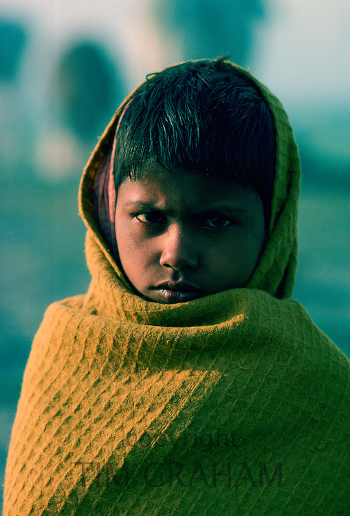Boy wrapped against the chill morning, Delhi, India