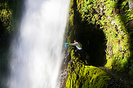 A young woman, fills her water bottle under the cold clear waters of Tunnel Falls on Eagle Creek trail in the Columbia River Gorge, Oregon, USA. Tunnel Falls received its name due to a tunnel being cut from the bedrock behind the falls so that hikers and trail runners can pass further up the gorge.  The trail becomes very narrow during this section and it is necessary to hold onto a safety cable. (Model Released)