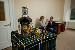 Pictured: Head of Whisky department Martin Green provides the background information on the decanter to receptionist Phillippa Iies over a glass.<br /><br />A rare, independently bottled Bowmore Dynasty Decanter-31 year old, estimated at £6,000-8,000, leads the next Bonhams Whisky sale <br /> <br />The whisky was bottled by the Glasgow company Hart Brothers Ltd in a crystal decanter made by the prestigious Portuguese glassware manufacturer Atlantis Crystal. The hall marked, sterling silver casing incorporates gilt mounted medallions of the monarchs of The Royal House of Stuart. The decanter is number 121 of 500.<br />Ger Harley | EEm 14 September 2021