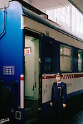 A train conductor stands at the entrance to a carriage waiting for departure, China