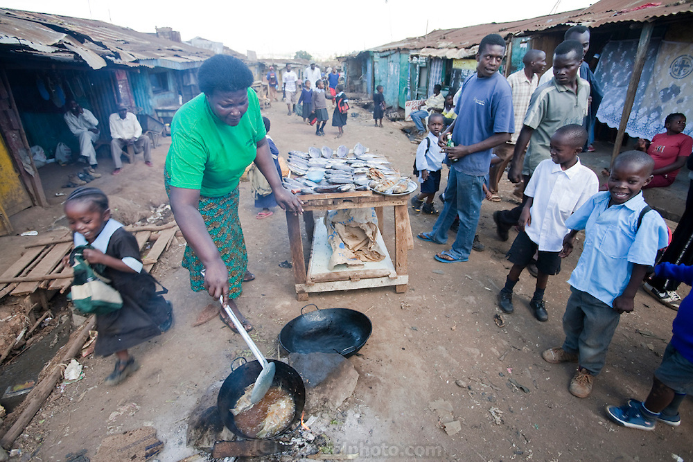 Roseline Amondi (right), a microloan recipient and mother of four, fries tilapia for sale in the Kibera slum in Nairobi, Kenya. (Roseline Amondi is featured in the book What I Eat: Around the World in 80 Diets.)