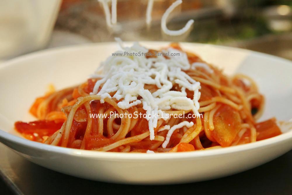 Preparing Spaghetti and marinara sauce adding the Parmesan Cheese