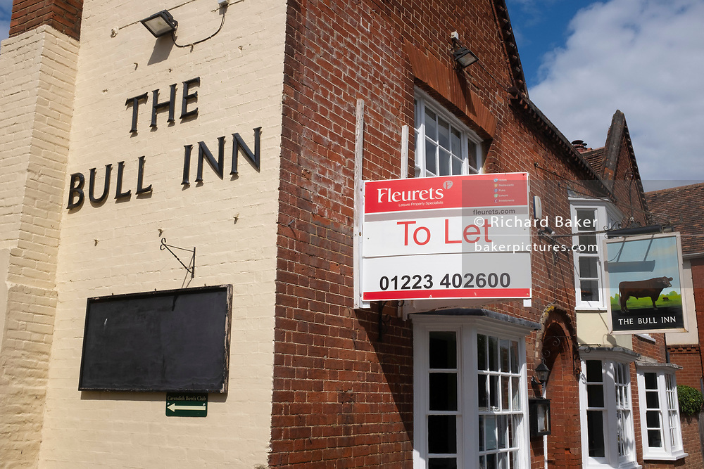 An estate agent's sign outside the Bull Inn, a property in the village of wool town Cavendish, on 10th July 2020, in Lavenham, Suffolk, England. Cavendish was home to Sir John Cavendish, the ancestor of the Dukes of Devonshire, who was involved in suppressing the Peasants' Revolt. Wat Tyler, the peasants' leader, was arrested by William Walworth, the Mayor of London, for threatening King Richard II in 1381. The wool trade was already present by the 13th century, steadily expanding as demand grew. By the 1470s Suffolk produced more cloth than any other county.