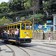 The Bondinho, tram or trolley car heads along the streets of Santa Teresa in the hills of Rio de Janeiro. The trap ride from the City Centre across the Lapa Aquaduct is popular for both tourists and locals. Rio de Janeiro,  Brazil. 20th September 2010. Photo Tim Clayton.