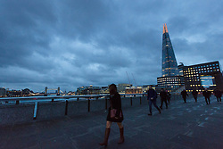 © Licensed to London News Pictures. 23/02/2017. LONDON, UK.  Storm clouds at first light behind Tower Bridge as early morning commuters cross London Bridge during windy weather as Storm Doris hits London and the south of England.  Photo credit: Vickie Flores/LNP