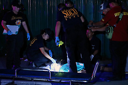 November 14, 2016 - Philippines - (EDITOR'S NOTE: Image depicts death) Members of S.O.C.O. (Scene of the Crime Operatives) and Philippine National Police (PNP) investigator process of the crime scene and un-mask the face of one of two un-identified summary execution victims at Diokno Blvd. Brgy 76, Zone 10, Pasay City. It'Äôs a part of the total out war campaign by the government about illegal drugs. (Credit Image: © Gregorio B. Dantes Jr/Pacific Press via ZUMA Wire)