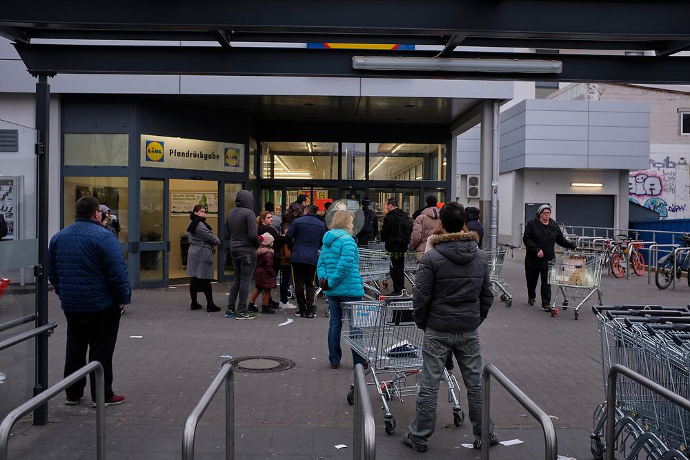 DEUTSCHLAND, Berlin, Wedding, 20.03.2020. Coronavirus-Pandemie: Social Distancing bei Lidl: Ein Schild weist darauf hin, dass sich aufgrund von Covid-19 maximal 70 Kunden im Laden aufhalten duerfen. Ein Wachmann kontrolliert den Einlass.