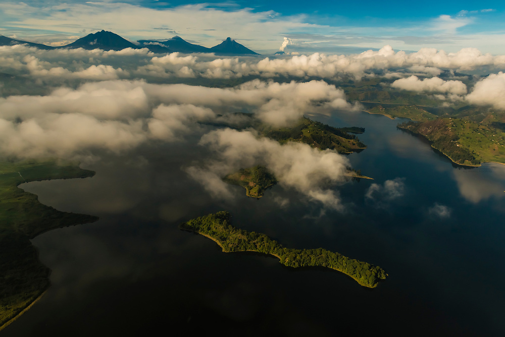A layer of clouds above Lake Mutanda, Uganda with Mt. Muhabura, Mt. Gahingqa and Mt. Sabyinyo in the Virunga Mountains in the background. The Virunga Mountains are a chain of volcanoes in East Africa, along the northern border of Rwanda, the Democratic Republic of the Congo and Uganda. The mountain range is a branch of the Albertine Rift Mountains, which border the western branch of the East African Rift. They are located between Lake Edward and Lake Kivu.