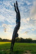 """Old Westbury, New York, U.S., September 1, 2019. """"Athlete III - Deep Plunge"""" is one of 33 outdoor sculptures by Jerzy Kedziora (Jotka), b. 1947 in Poland,, and his Balance in Nature art is on view at historic Old Westbury Gardens in Long Island, until October 20, 2019. Seen almost silhouetted by the sky at dusk, the life-size, bronze resin balancing sculpture, dressed in blue swimwear, appears about to dive into the lawn."""