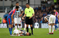 Newcastle United's Ayoze Perez lies injured on the pitch as Referee Andre Marriner speaks to Crystal Palace's Andros Townsend during the Premier League match at Selhurst Park, London.