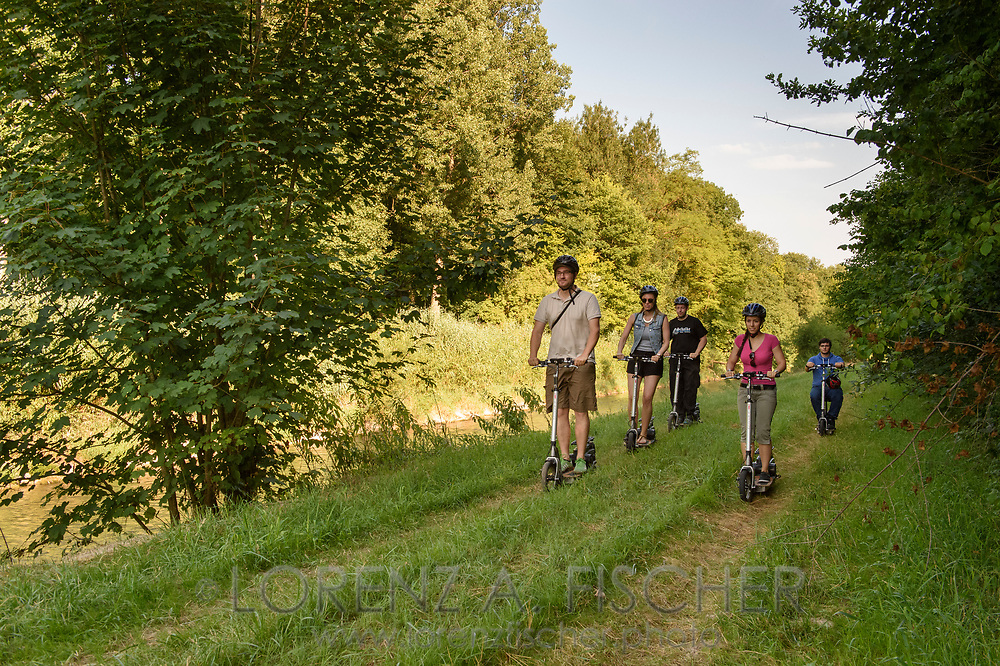 A group of young people is enjoying a drive with a Trivanti, an electro scooter, on the roads of the Allmend of Frauenfeld on a nice and sunny evening in July, Thurgau, Switzerland
