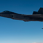 U.S. Air Force F-22 Raptors flies off the wing of a USAF KC-135 Stratotanker while his wingman fuels. The F-22s are on their way to join a strike involving other coalition aircraft to destroy a Vehicle Borne Improvised Explosive Device factory, Jan 30, 2015, in Iraq. The U.S. led coalition has been conducting air strikes against the Da'esh since August 2014. (U.S. Air Force Photo by Staff Sgt. Perry Aston/Not Reviewed)