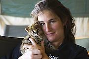 Serval<br /> Felis serval<br /> Suzi Eszterhas (Photographer/foster mom) with 2.5 week old orphan kitten<br /> Tanzania
