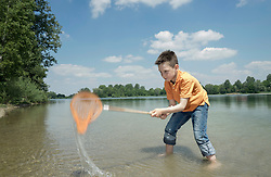 Boy catching fish with a brailer in the lake, Bavaria, Germany