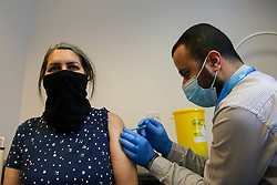 © Licensed to London News Pictures. 29/05/2021. London, UK. Pharmacist Huseyin Akpinar administers the AstraZeneca vaccine to a woman at a vaccination centre in Tottenham, north London. Public Health Covid-19 vaccination centre in Tottenham, north London. Public Health England data shows that just under 7,000 cases of the Indian variant have been confirmed in the UK. Photo credit: Dinendra Haria/LNP