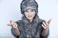 studio shot portrait of a beautiful woman russian type in a fur coat and hat opening her arms in sign of welcome