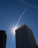 Contrail with sunlight over Bank Of America building in downtown Tucson