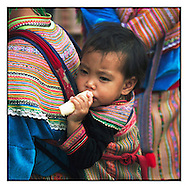 Small kid of a Hmong flower minority carried in the back of his mother, eats a banana. Market of Can Cau, close from Bac Ha, Vietnam.