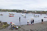 Boats moored in the sea at Parrog as people on Summer holiday enjoy walking and playing around on the beach and sea on 17th August 2021 in Pembrokeshire, Wales, United Kingdom. Newport is a town, parish, community, electoral ward and ancient port of Parrog, on the Pembrokeshire coast in West Wales at the mouth of the River Nevern in the Pembrokeshire Coast National Park.
