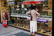 Women look at the window of a shop saying liquidation: closing down, a signifier of the precarious state of Argentina's economy, Buenos Aires, Argentina.