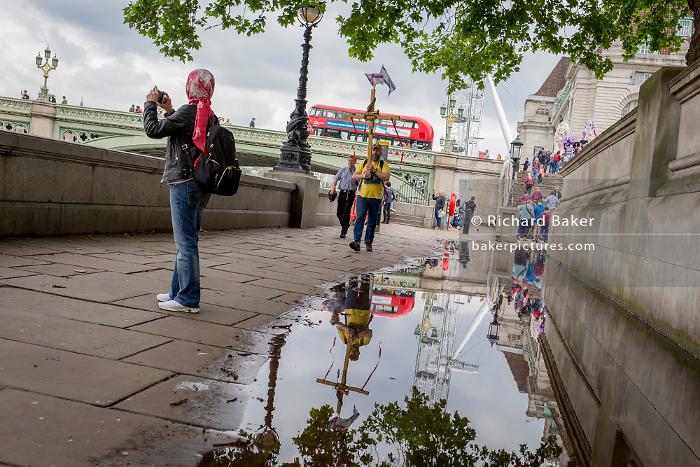 After heavy rainfall the day before, passers-by are reflected in a puddle on the Albert Embankment on the Lambeth side of Westminster Bridge, on 11th June 2019, in London, England.